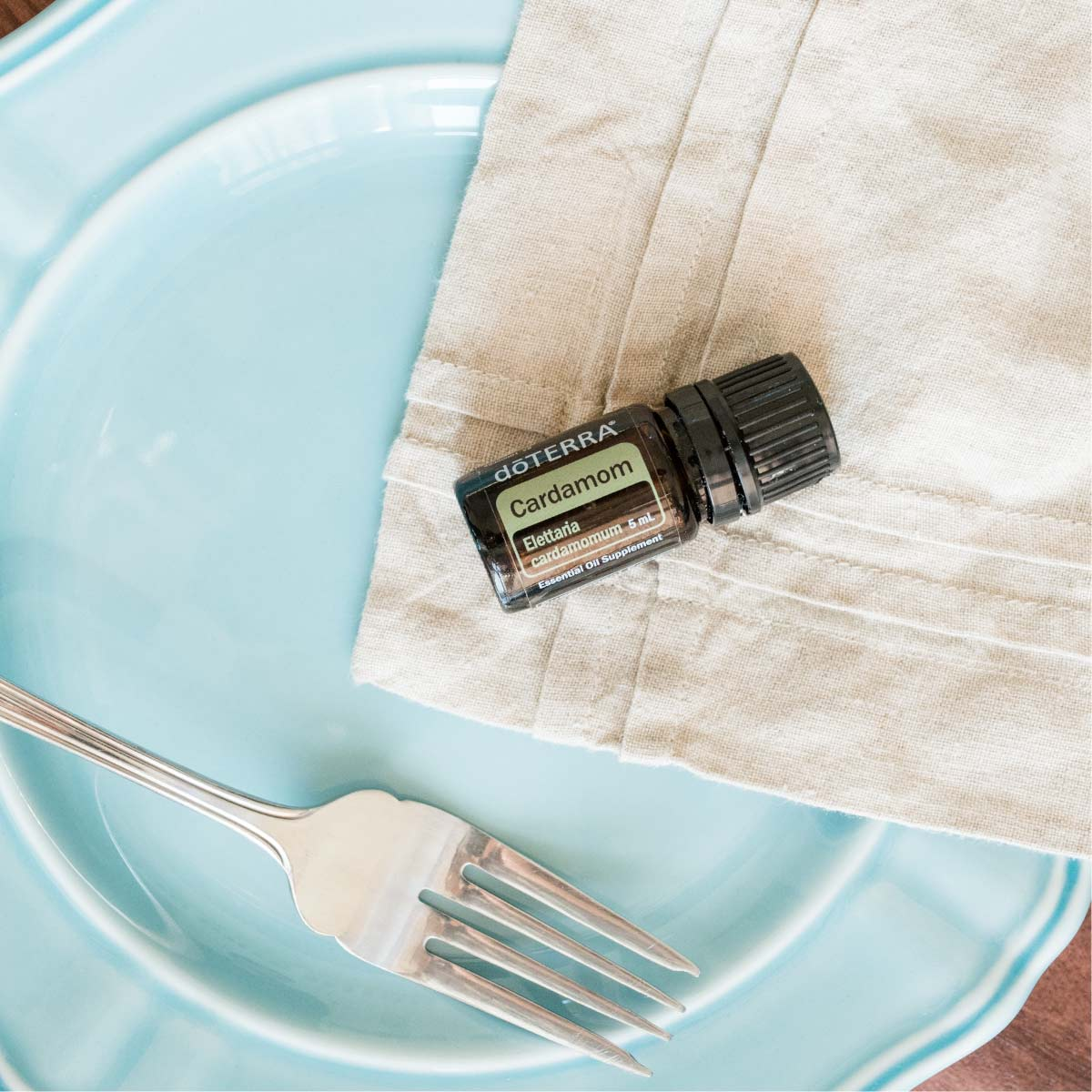 Bottle of Cardamom oil next to a dinner plate, fork, and napkin. What does Cardamom oil smell like? Cardamom essential oil has a warm aroma that is both spicy and sweet.