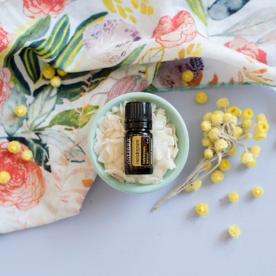 Bottle of doTERRA Helichrysum oil, little yellow flowers, and floral tablecloth. Many people use Helichrysum essential oil for skin, for a soothing massage, or for internal benefits.