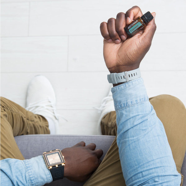 Man holding bottle of doTERRA Cypress oil. There are many benefits of cypress oil. This essential oil is known to be balancing, comforting, invigorating, and good for the skin.