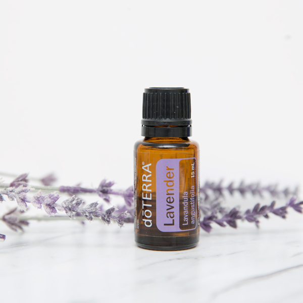 Lavender sprigs, bottle of doTERRA Lavender essential oil. Wondering how to use lavender oil for skin? Lavender oil can be added to your daily facewash or moisturizer, or applied directly to skin imperfections to promote a healthy-looking complexion.