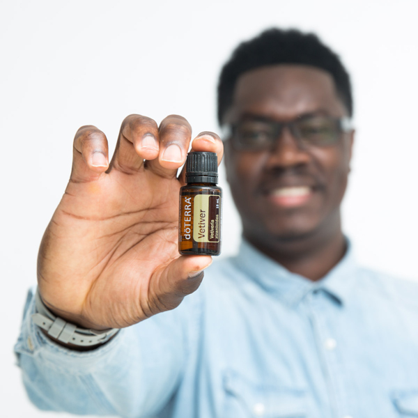 Man holding bottle of doTERRA Vetiver essential oil. What are the health benefits of vetiver oil? Vetiver oil holds many benefits for the skin, emotions, and body. Keep reading to learn more about vetiver oil benefits and uses.