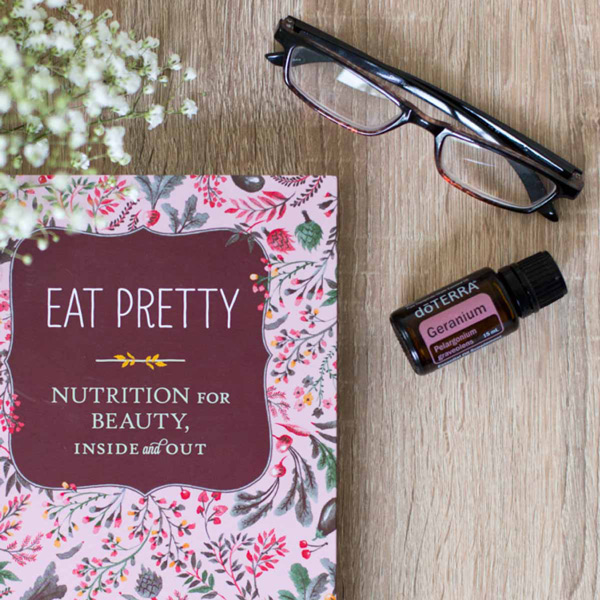 Geranium essential oil bottle, small white flowers, a pair of reading glasses, a book titled, Eat Pretty: Nutrition for Beauty, Inside and Out. What does Geranium oil smell like? Geranium essential oil has a sweet, floral aroma that is both herbaceous and rose-like.