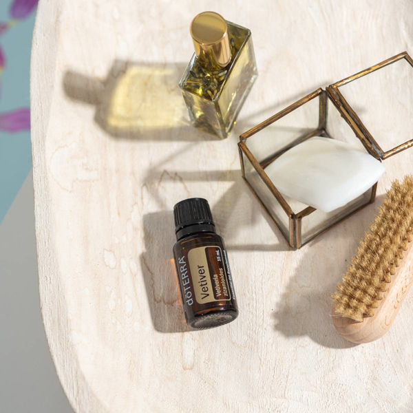 Vetiver essential oil bottle on a table next to perfume, jewelry box, and brush. What is vetiver oil used for? Vetiver oil can be used to improve mood, promote a restful sleep, soothe the muscles, and more.