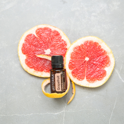 Two slices of grapefruit, grapefruit peel, and a bottle of Grapefruit oil. Grapefruit essential oil can be used for things like skin care, weight management, and uplifting emotions.