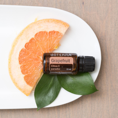 Slice of grapefruit, Grapefruit oil bottle, and green leaves on a plate. The uplifting, energizing, and invigorating nature of Grapefruit essential oil makes it one of doTERRA's top selling essential oils.