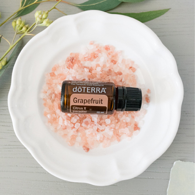 Botella de aceite de Pomelo en un plato blanco. Use aceite esencial de Pomelo para la piel, el control de peso o el estado de ánimo.