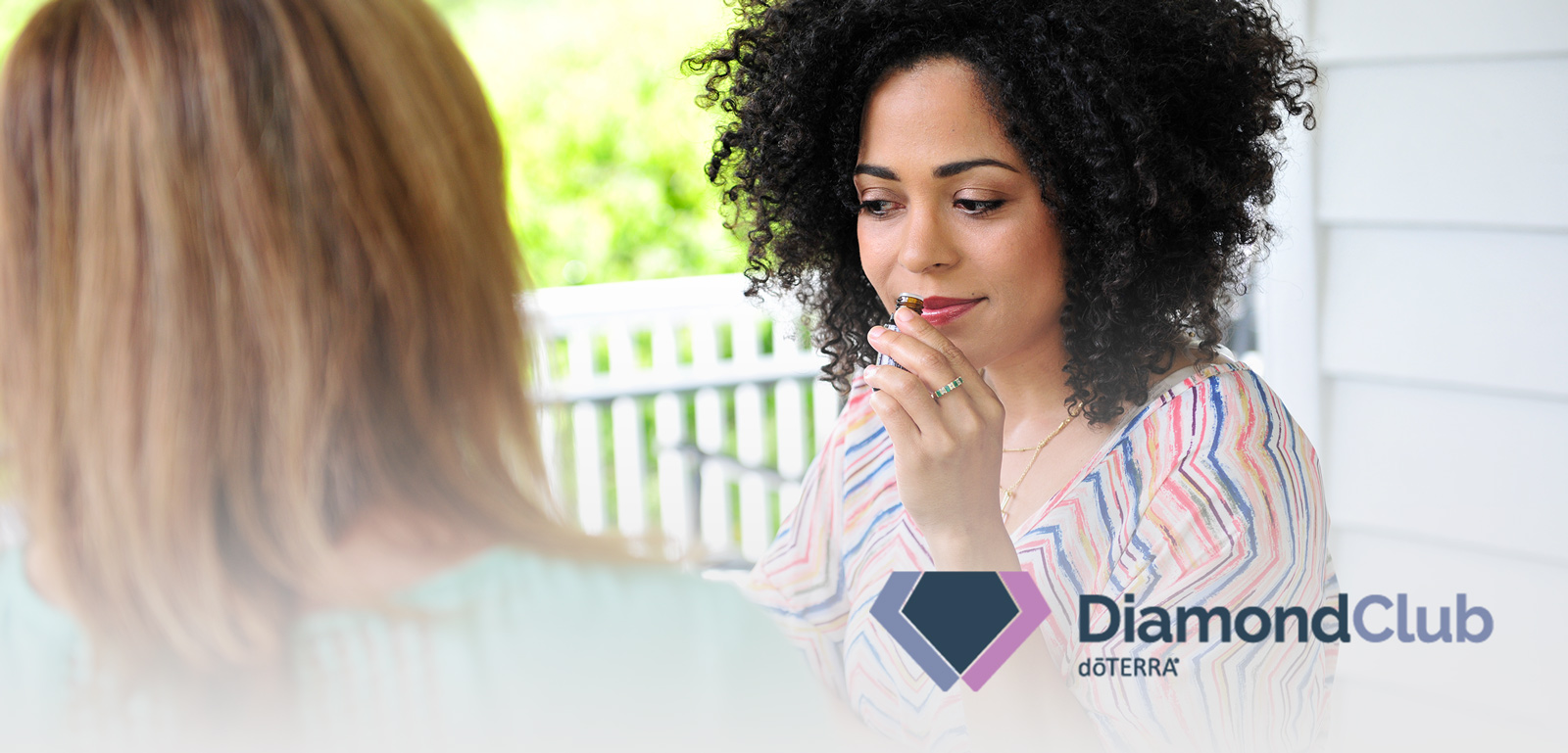 What are the benefits of doTERRA Diamond Club? Woman outside on porch smelling essential oil bottle.