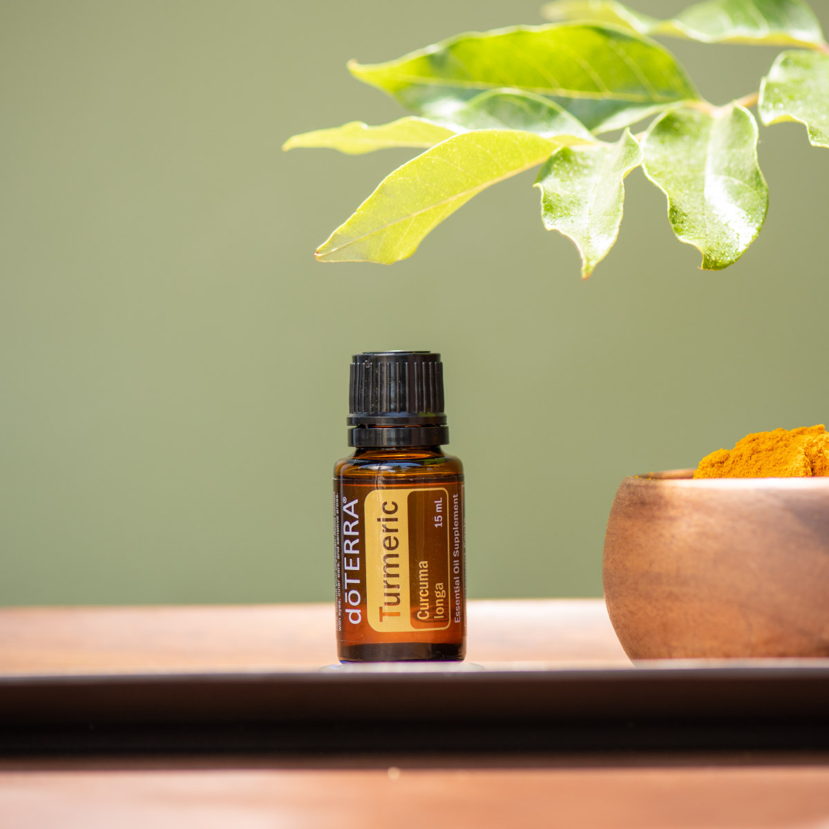 Bottle of Turmeric essential oil next to brass bowl and green leaf. What are the benefits of Turmeric oil? Turmeric oil has internal benefits for the nervous system and immune system, plus it holds benefits for the skin when applied topically.