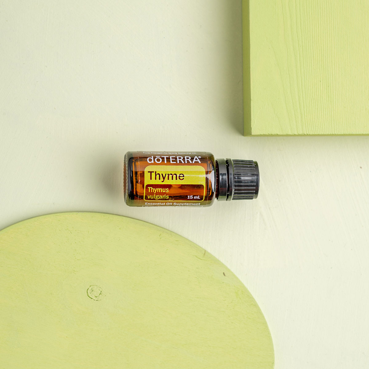 Bottle of Thyme oil next to green wood circle and green wood square. What are the benefits of Thyme essential oil? Thyme essential oil has benefits for the immune system, plus it provides antioxidants and can help to repel insects.