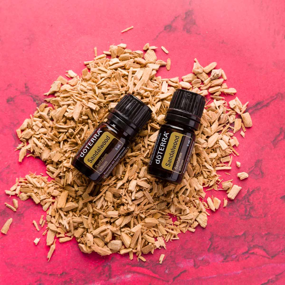 Two bottles of Sandalwood oil resting on a pile of wood shavings. How do I use Sandalwood essential oil? Sandalwood essential oil can be used to promote healthy looking skin, to create a calming environment, or to promote grounding feelings during meditation.