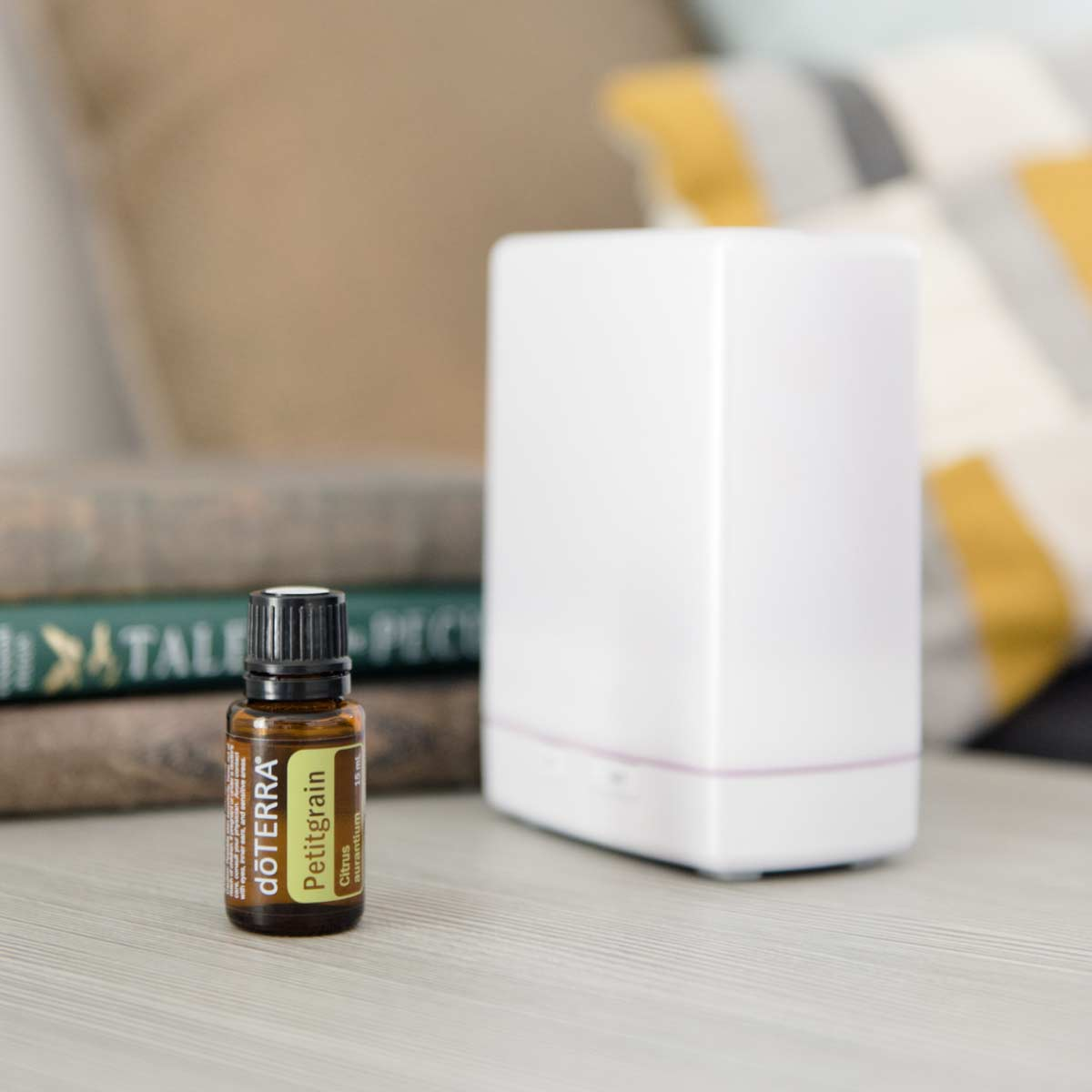 Bottle of Petitgrain essential oil next to essential oil diffuser and a stack of books. What are the benefits of Petitgrain essential oil? Petitgrain oil has benefits for relaxation, the immune system, and for sleep.