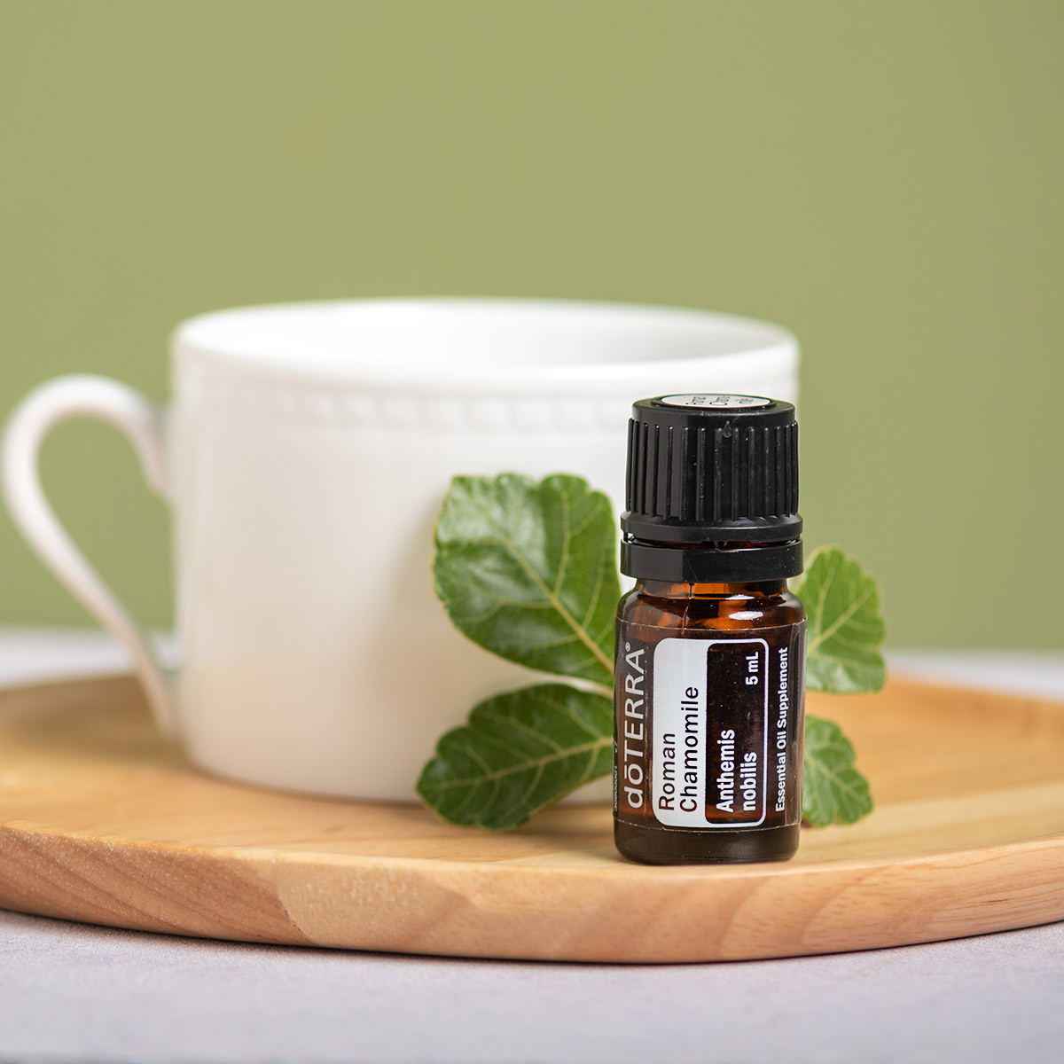 Bottle of Roman Chamomile essential oil next to a white teacup and green leaves. Roman Chamomile oil