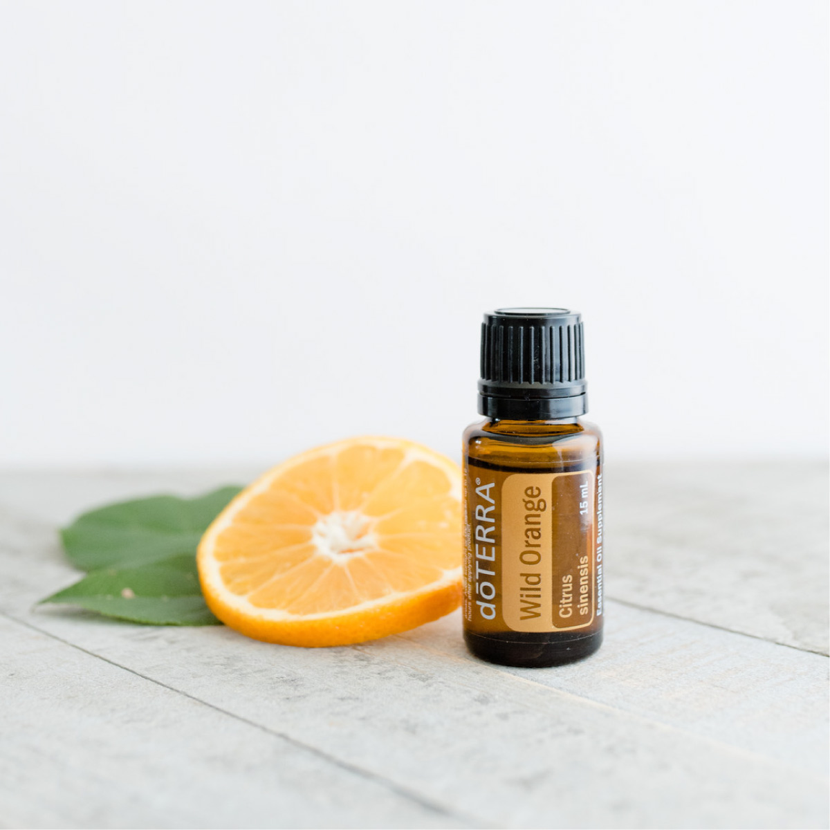 Bottle of doTERRA Wild Orange oil next to a fresh orange slice and green leaves. What are the best ways to use Wild Orange essential oil? People like to use Wild Orange oil for cleansing surfaces around the home, or internally to support a healthy immune system.