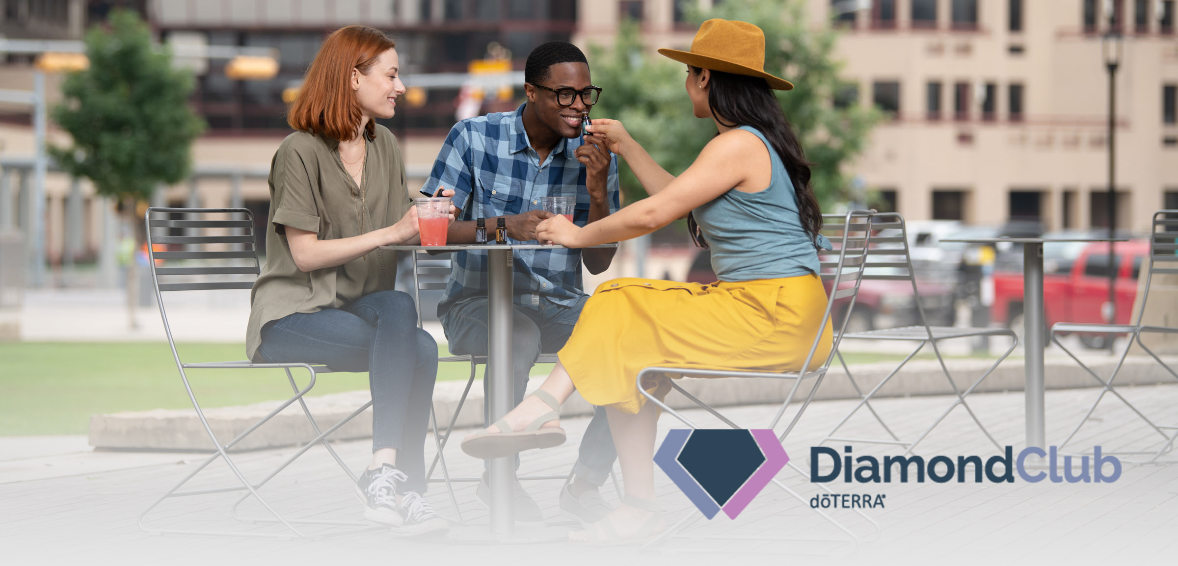 What is Diamond Club? Three individuals at a table enjoying drinks and sharing essential oils. Diamond Club logo in lower right corner.